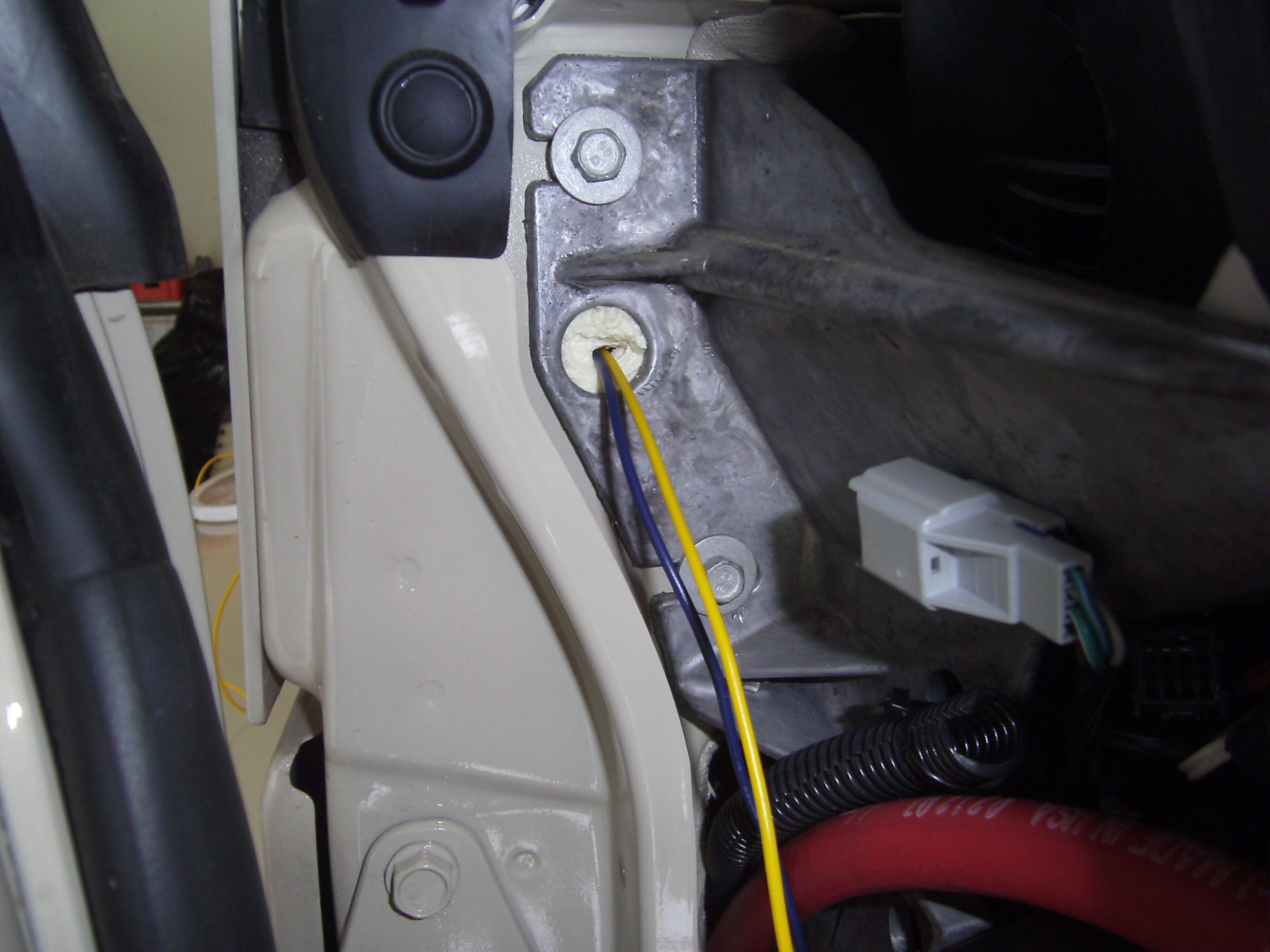 It is filled with whitish-yellowish foam insulation, but you can push the  wire through and it goes to the engine ...